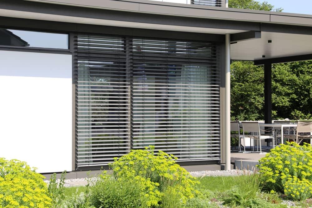 Außenansicht halbgeöffnetes Raffstore am Fenster zur Terasse